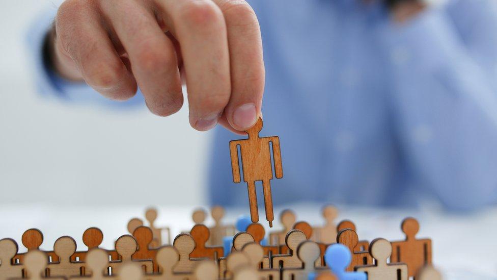 Mão levanta um boneco de papel de grupo com dezenas de figuras semelhantes