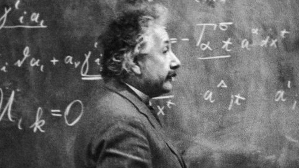 Albert Einstein standing beside a blackboard