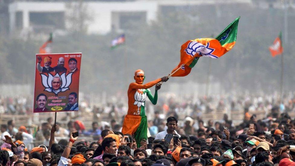 Pendukung Bharatiya Janata (BJP) mengibarkan bendera