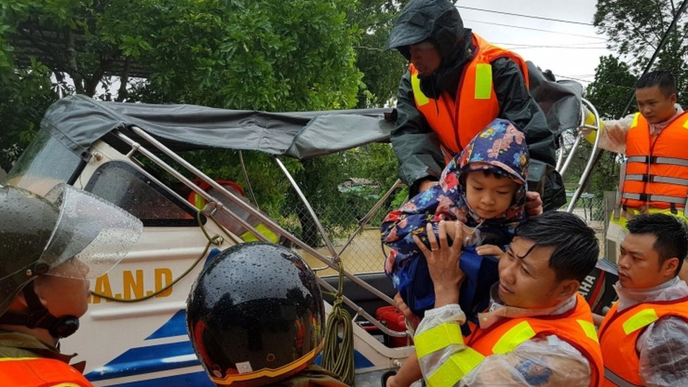 Municipal workers evacuate local people from flood water in Quang Tri province, Vietnam, on 18 October 2020