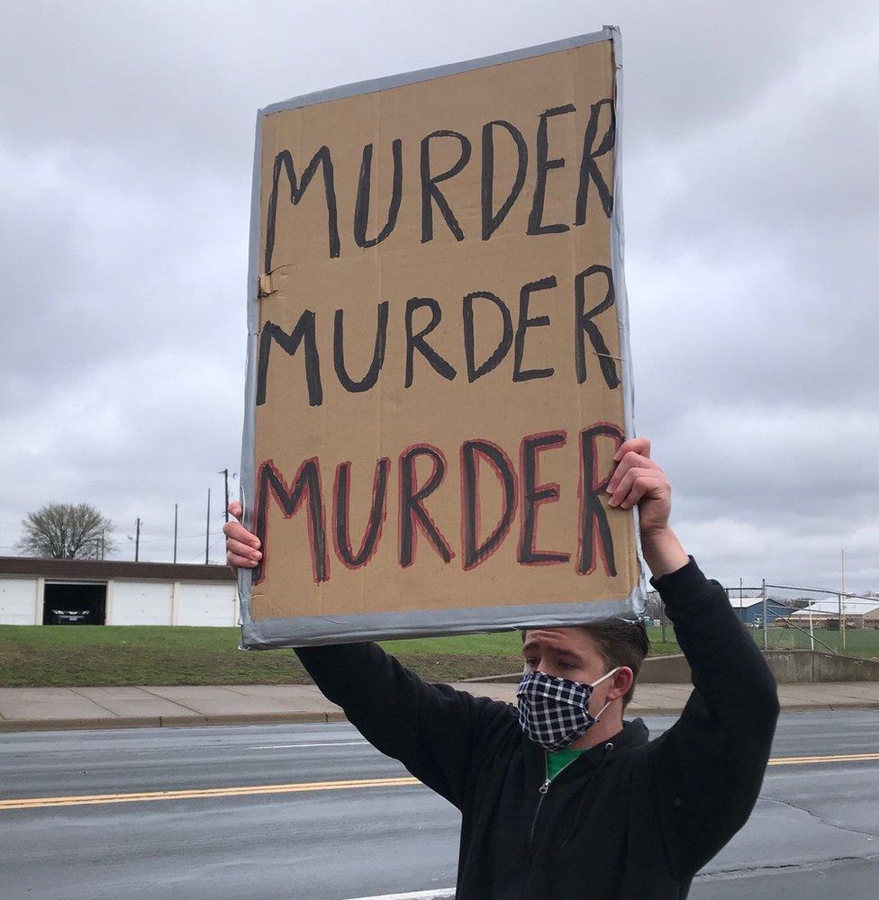 """Manifestante a las afueras del Departamento de Policía de Brooklyn Center con un cartel que pone """"Asesinato, Asesinato, Asesinato"""""""