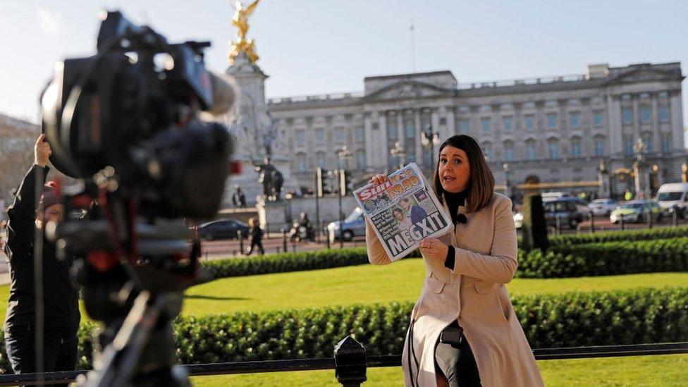 Una reportera informa sobre el anuncio de Meghan y Harry frente al Palacio de Buckingham