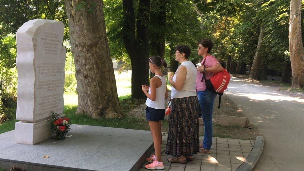 Spomenik Dženanu Memiću na mestu stradanja u opštini Ilidža u Sarajevu oko kojeg se prolaznici mole.