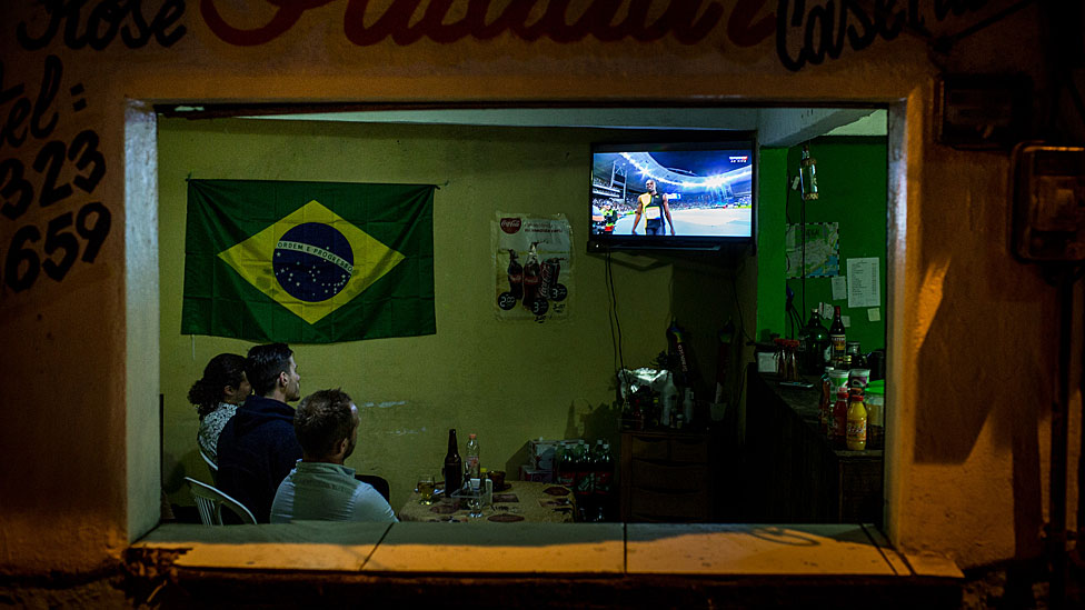 People watching the Olympics on TV in a Rio bar