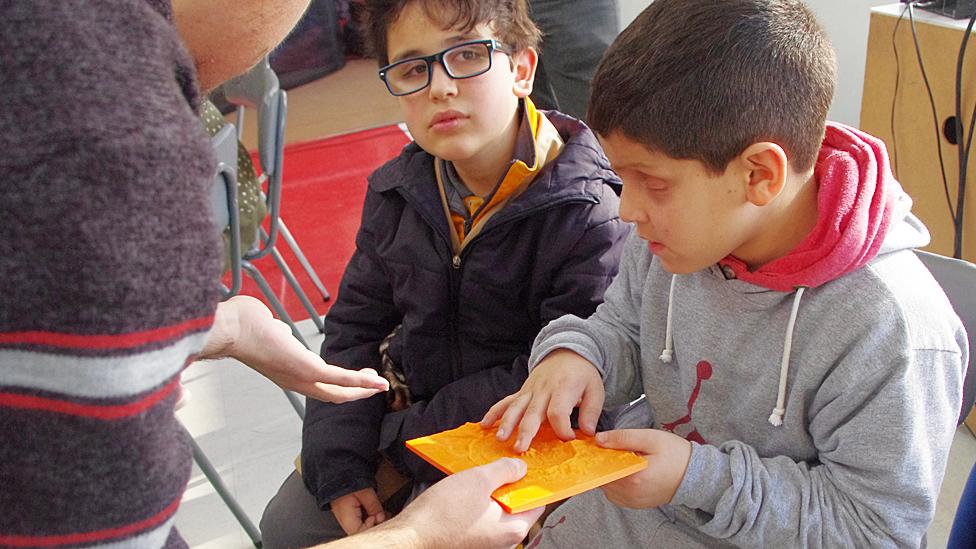 Niños tocando una maqueta que representa un cráter