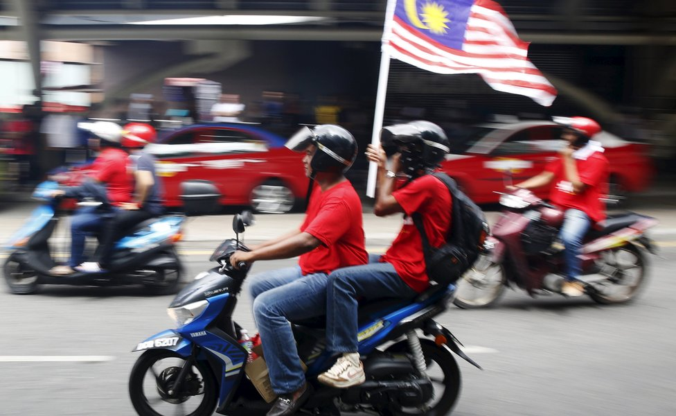 People on a motorbike with a Malaysian flag in KL (16 Sept 2015)