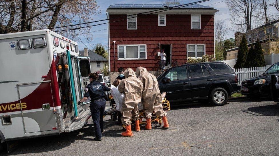 Paramédicos ingresando a una persona a una ambulancia.
