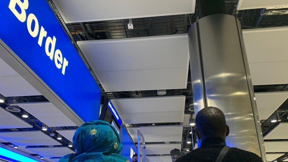 Passageiros sentados no controle da imigração em Heathrow, Londres