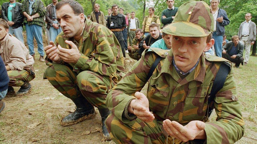 Soldados bosnios musulmanes rezando durante el funeral de otros tres soldados.