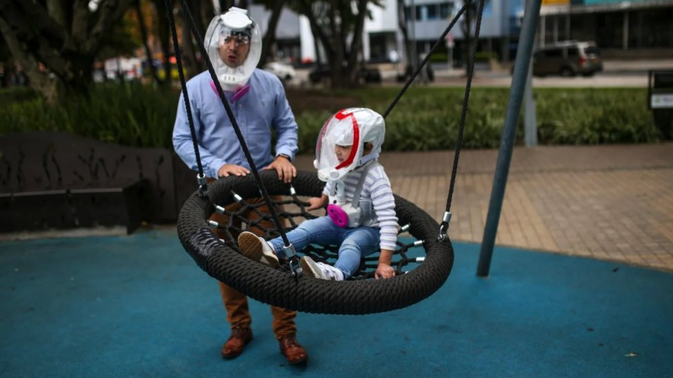 Father and son playing at a swing, wearing full face 'helmet-masks', and the little child has been dressed up so he looks like an astronaut