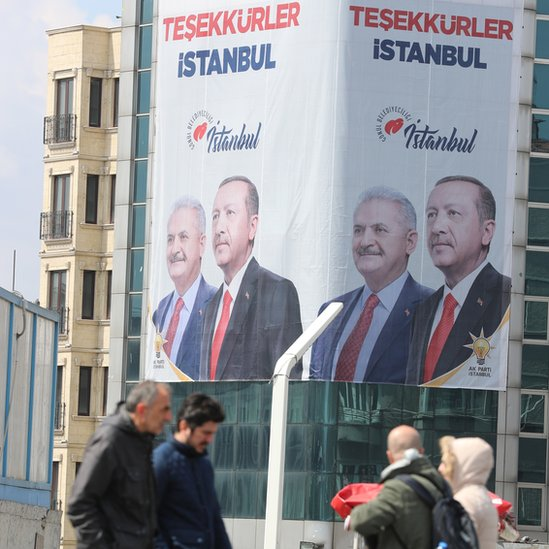 """People pass in front of a huge banner with pictures of Turkish President Recep Tayyip Erdogan and Binali Yildirim, candidate of Turkish ruling party Justice and Development Party (AK Party) reading on """"Thank you Istanbul"""" in Istanbul, Turkey, 03 April 2019"""