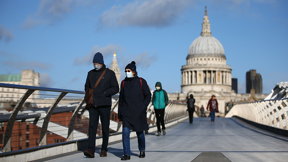 People in masks walk across Millennium Bridge away from St Paul's on a bright November morning