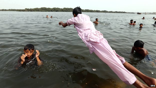 People jump in the water to cool off in Karachi