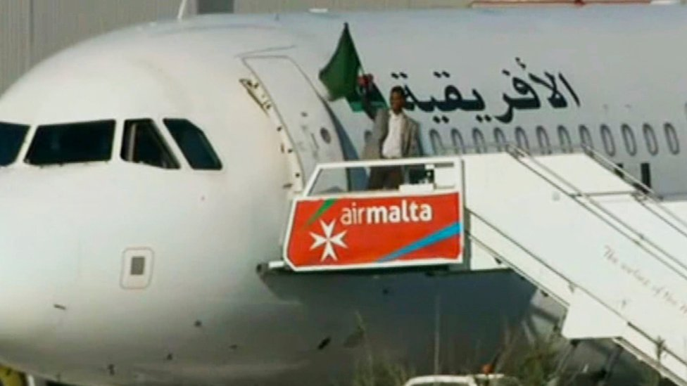 An Afriqiyah Airways plane stands on the tarmac at Malta International airport as an unidentified man waves a flag
