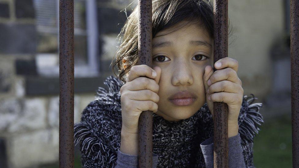 A girl holds prison bars