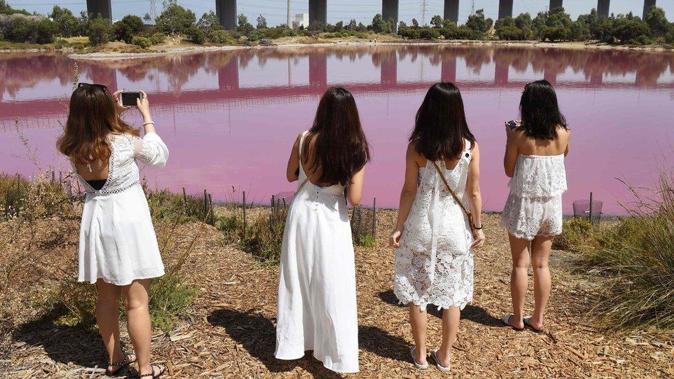 četiri žene u belom ispred jezera