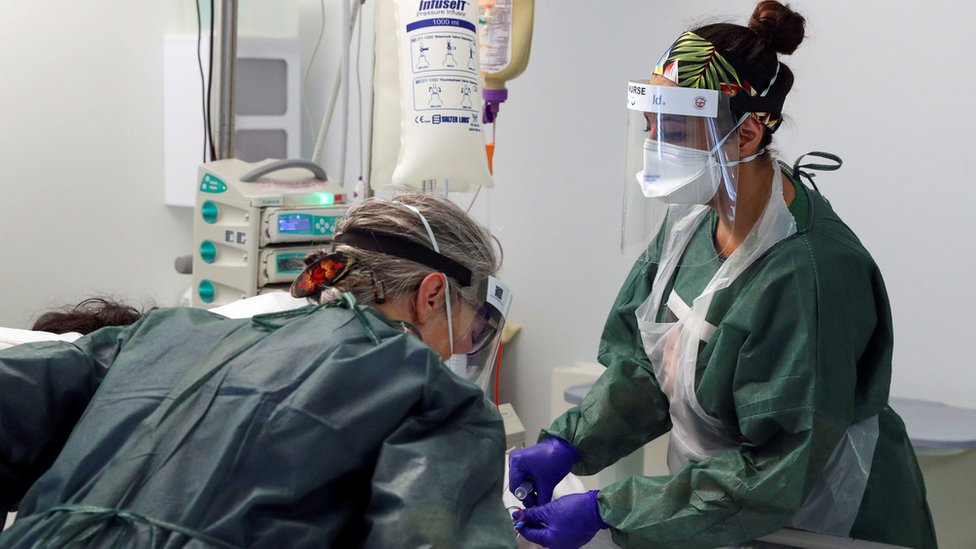 Nurses in personal protective equipment care for a patient