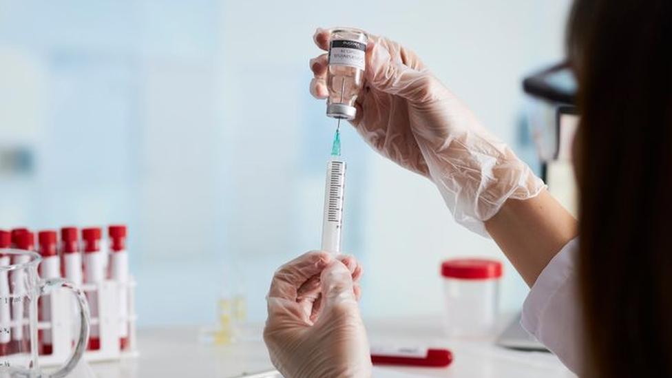Cientista segura uma seringa e extrai o líquido de uma ampola de vacina