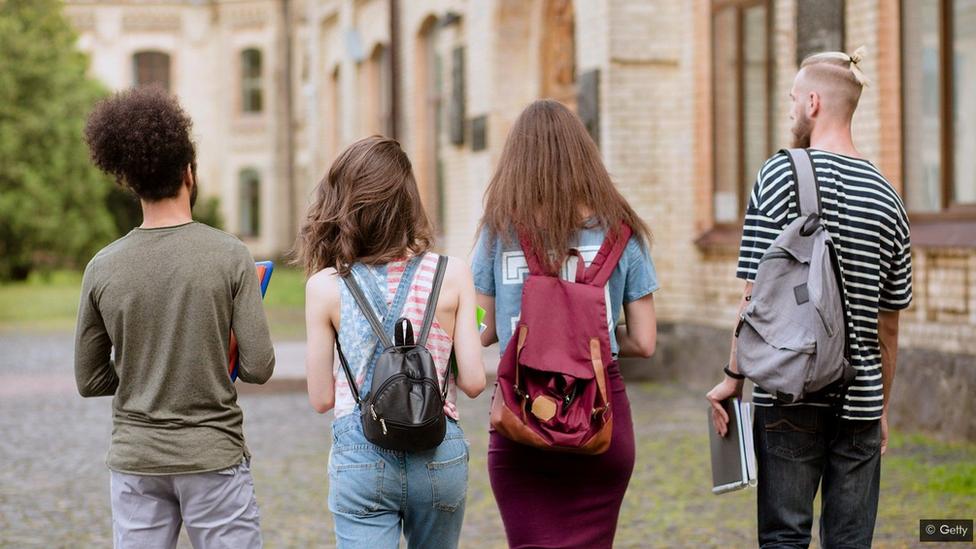 مجموعة من الطلاب الشباب يسيرون في الحرم الجامعي