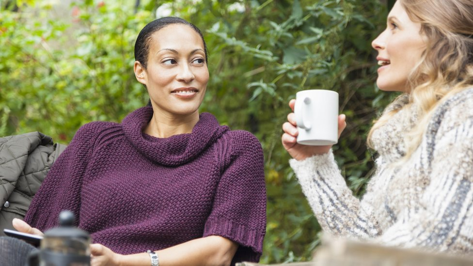 two women chatting, one holding phone