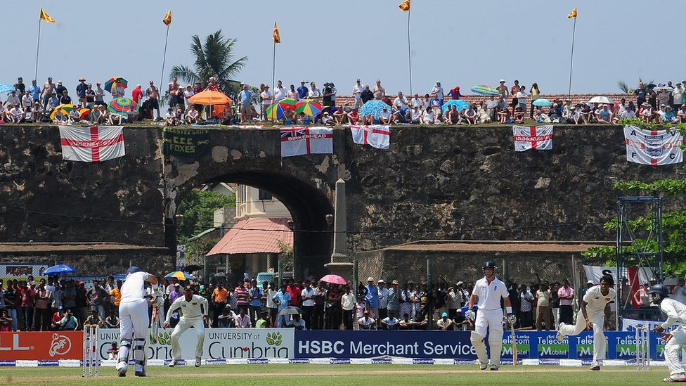 England cricket fans watch the second day of the opening Test match between Sri Lanka and England from the top of the 17th century Dutch fort overlooking Galle Stadium in Galle (27 March 2012)