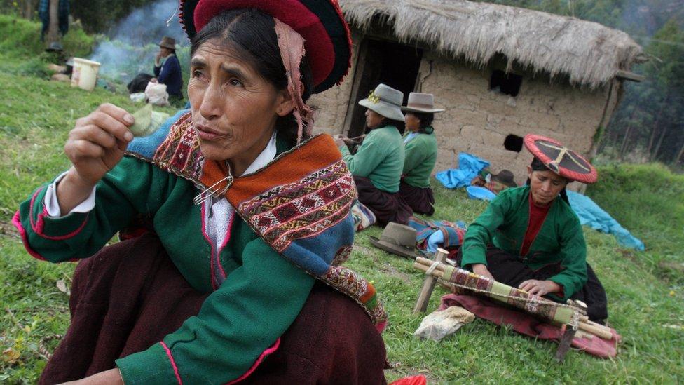 Mujer sosteniendo una hoja de coca