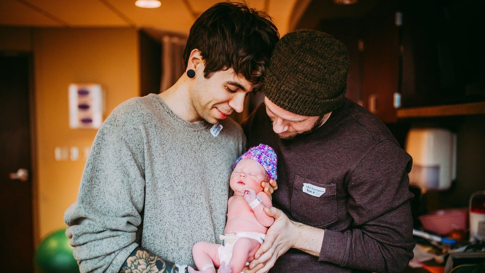 Baby Uma held by her parents Elliot Dougherty and Matthew Eledge.