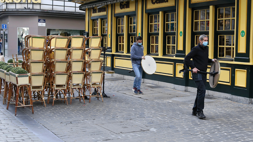 People carrying tables outside a closed restaurant in Brussels, Belgium