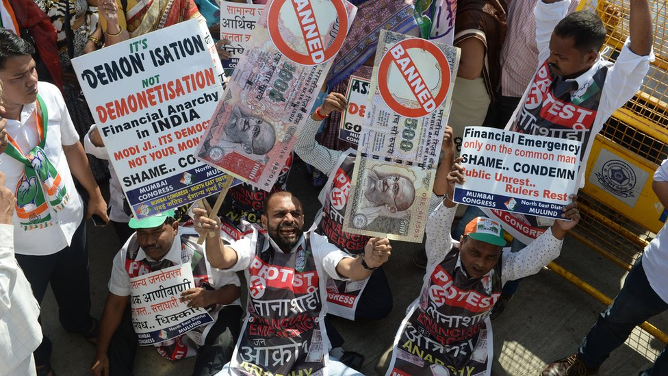 An Indian protestor holds placards of banned 500 and 1000 rupee notes during a protest against demonetisation, in Mumbai on November 28, 2016.