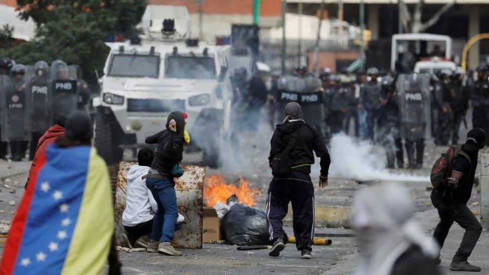 Manifestantes y policías en Venezuela