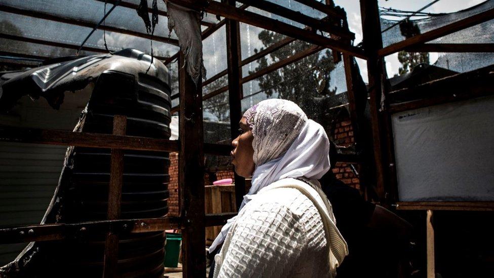 Una mujer mira el equipo quemado en un centro de tratamiento de ébola, que fue atacado en Butembo