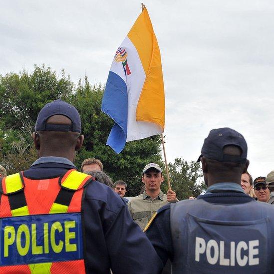 Sudafricanos que apoyan el movimiento de resistencia Afrikaner (AWB) de supremacistas blancos ondean la bandera que simboliza el apartheid frente a la policía en 2010.