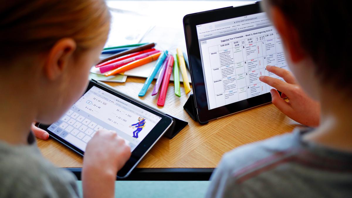 Niños utilizando tabletas para hacer la tarea