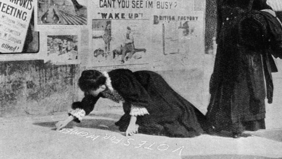 Annie Kenney painting a pavement with a slogan, 'Votes For Women' in 1907