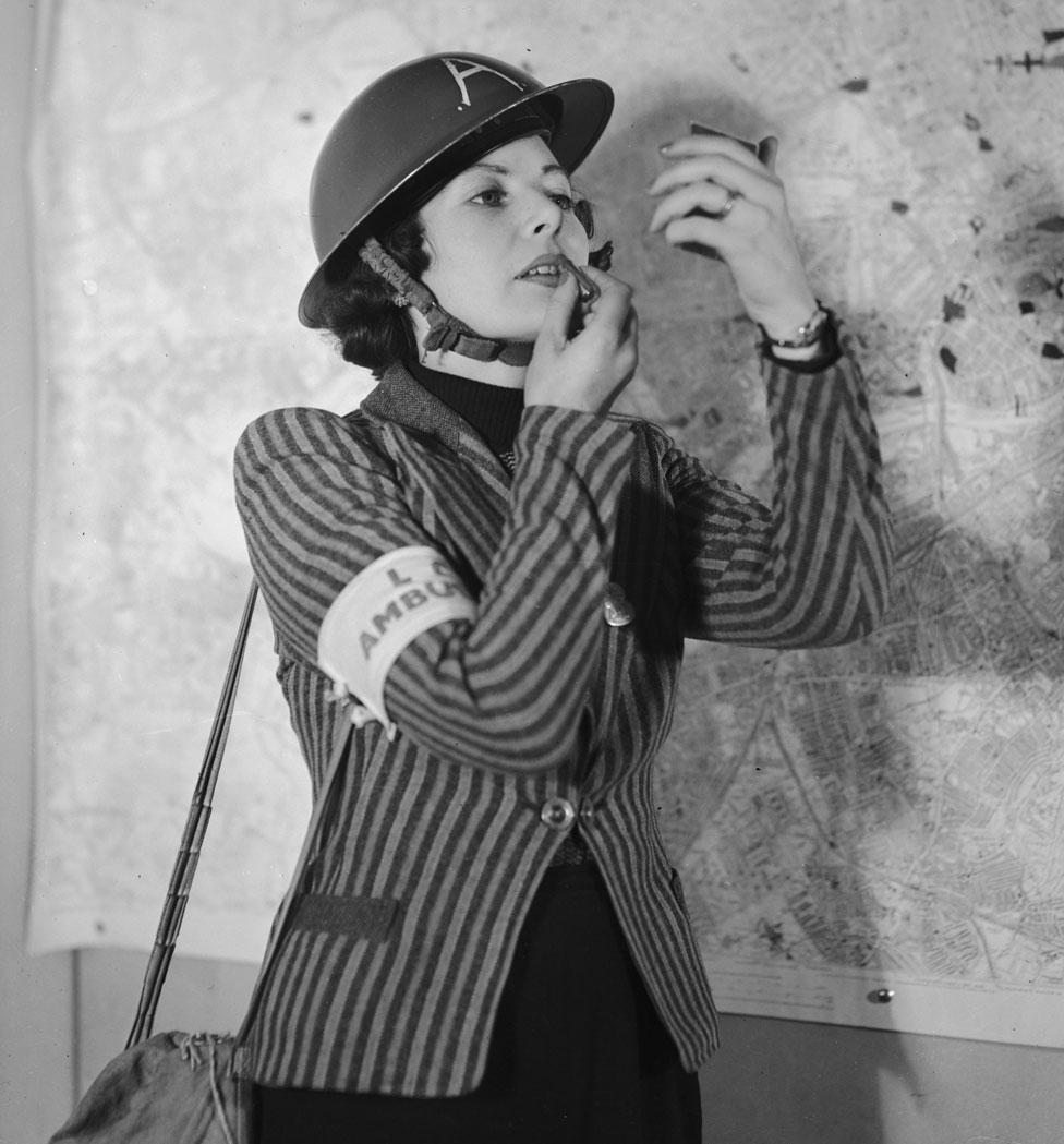 Una mujer se coloca lápiz labial en Londres en 1940.