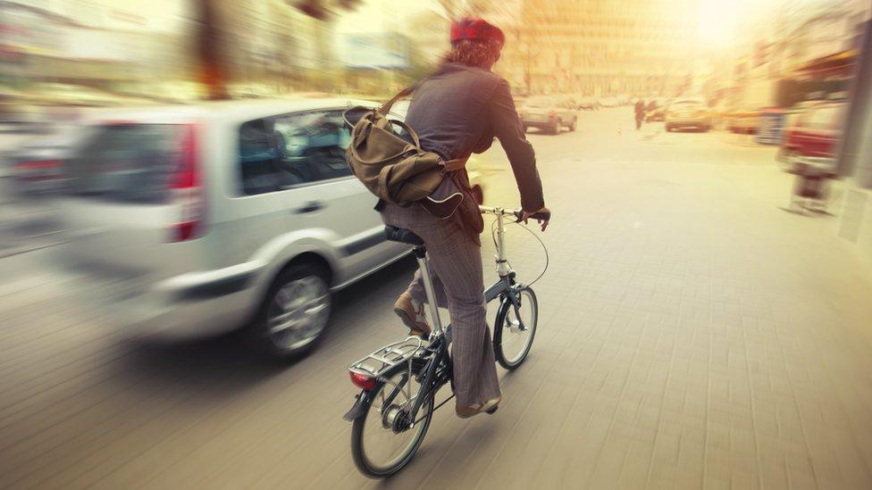 Cyclist on city road near car