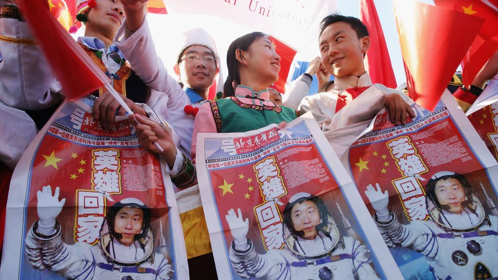 People hold up newspapers with the first Chinese man to go to space on the front page