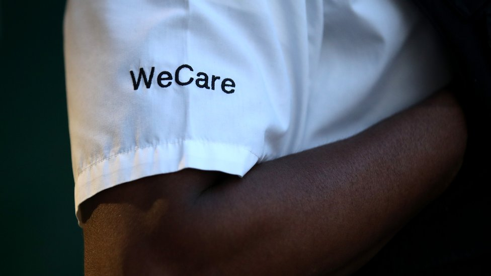 'We care' written on a white uniform of someone clapping