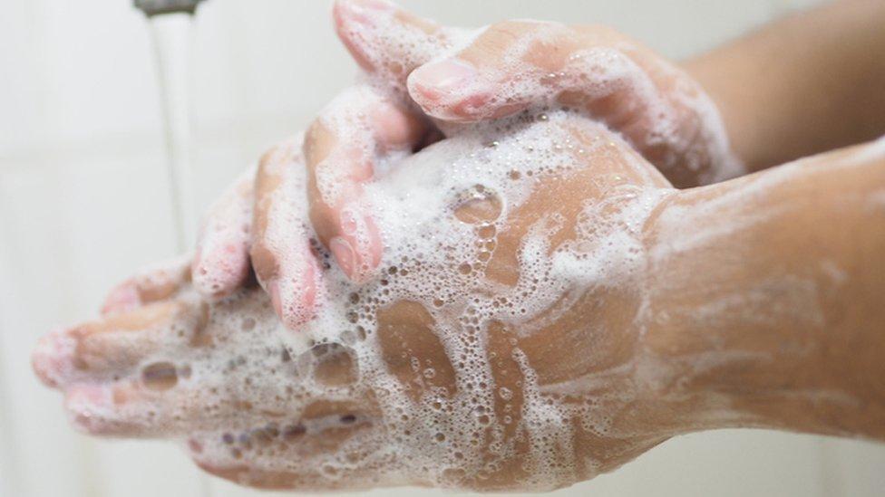 Persona lavándose las manos.