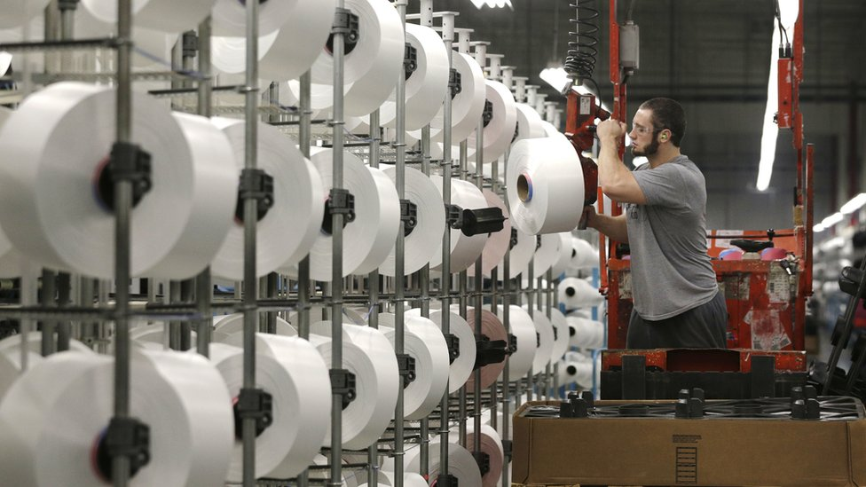 A machine worker unloads spools of thread at a US factory