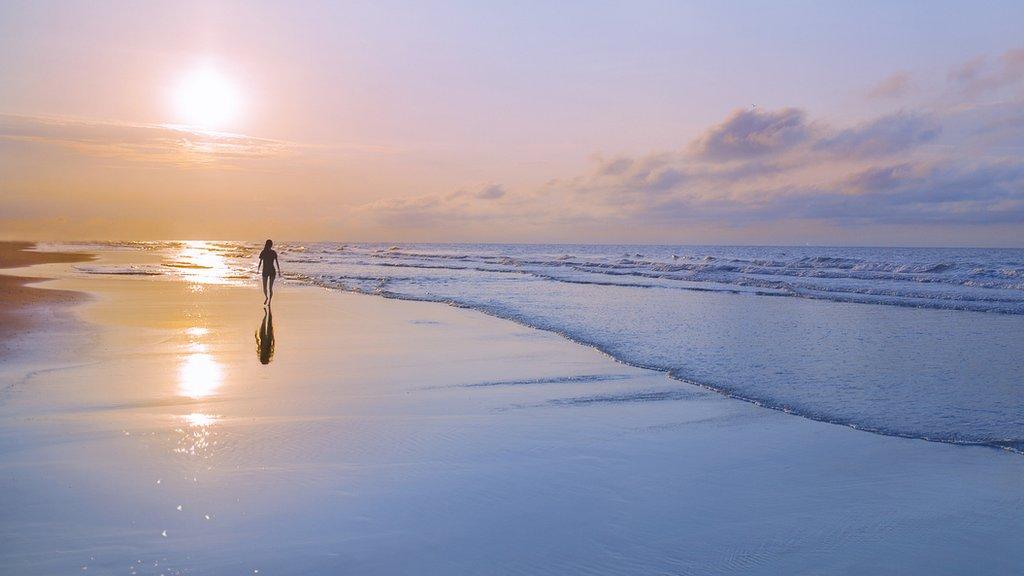 Persona caminando en playa al amanecer