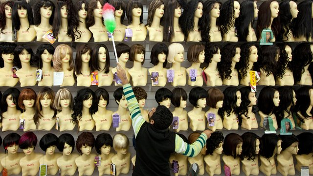 A man dusts in a wig shop