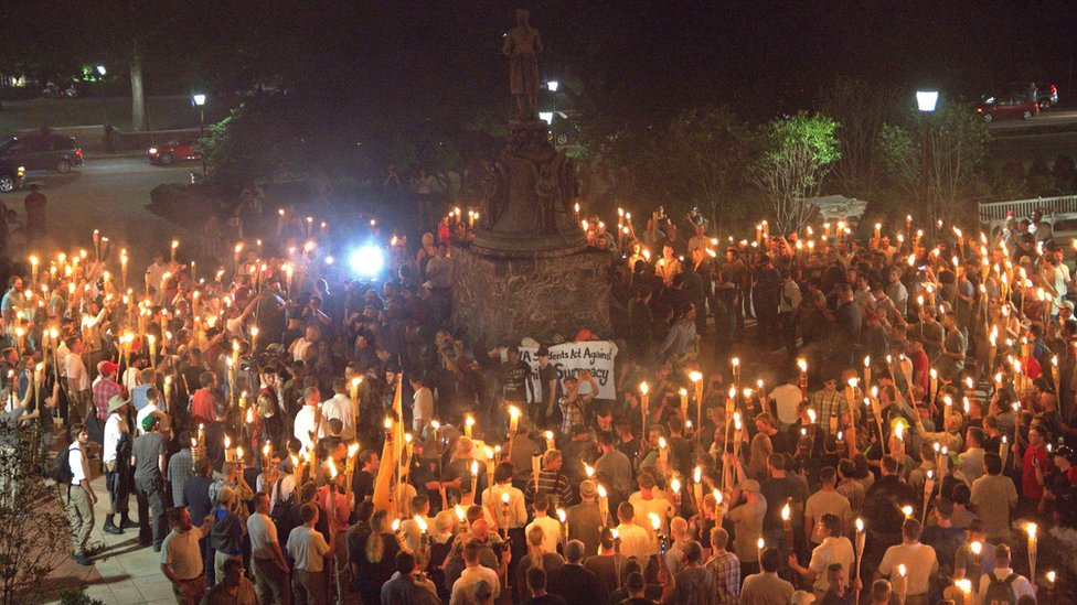 White nationalists carry torches around a statue of Thomas Jefferson on the grounds of the University of Virginia, surrounding a smaller group of counter protesters, 11 August 2017