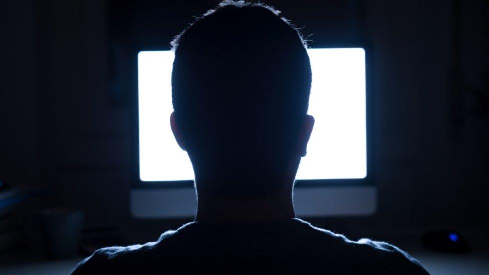 Hombre frente a una computadora