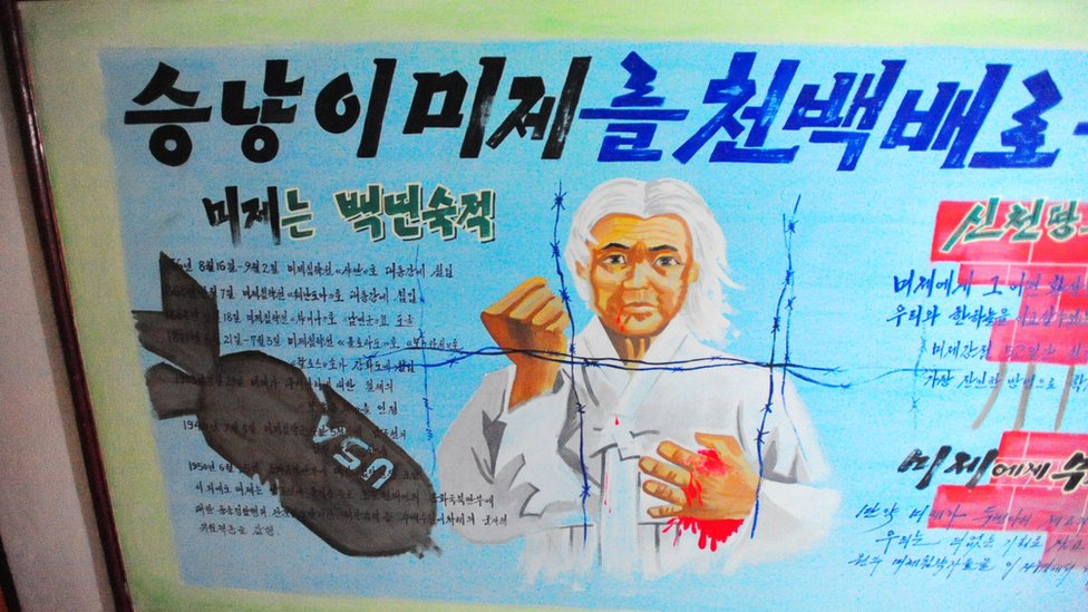 Poster of white haired man behind barbed wire balling wrist in defiance to Americans