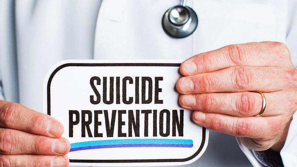 """Médico con cartel de """"Prevención de suicidios"""""""