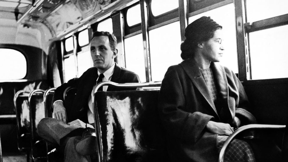Rosa Parks sits in the front of a bus in Montgomery, Alabama, after the Supreme Court ruled segregation illegal on the city bus system on December 21st, 1956. Man sitting behind Parks is Nicholas C. Chriss, a reporter for United Press International out of Atlanta.