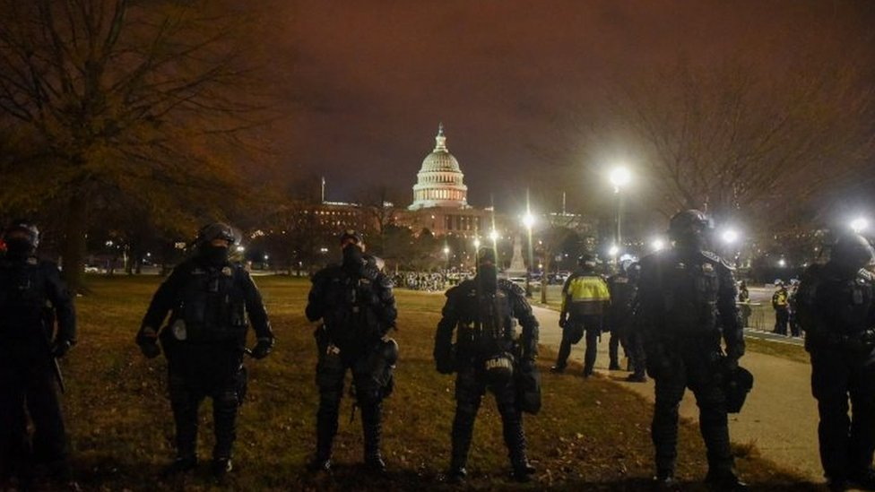 Police stand guard during the curfew overnight on Wednesday