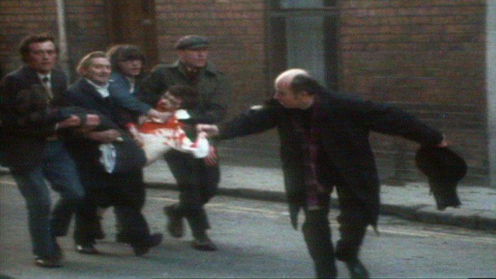 Un sacerdote agita un pañuelo manchado de sangre mientras cuatro hombres llevan a un hombre herido y ensangrentado por las calles de Londonderry durante The Troubles.