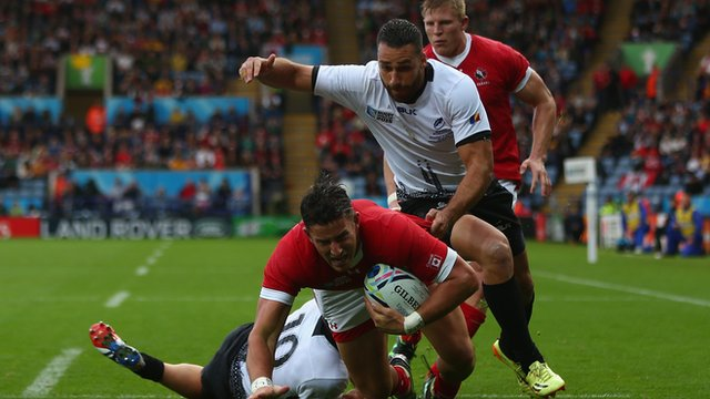 Van Der Merwe of Canada scores the opening try as Madalin Lemnanu of Romania challenges during the 2015 Rugby World Cup